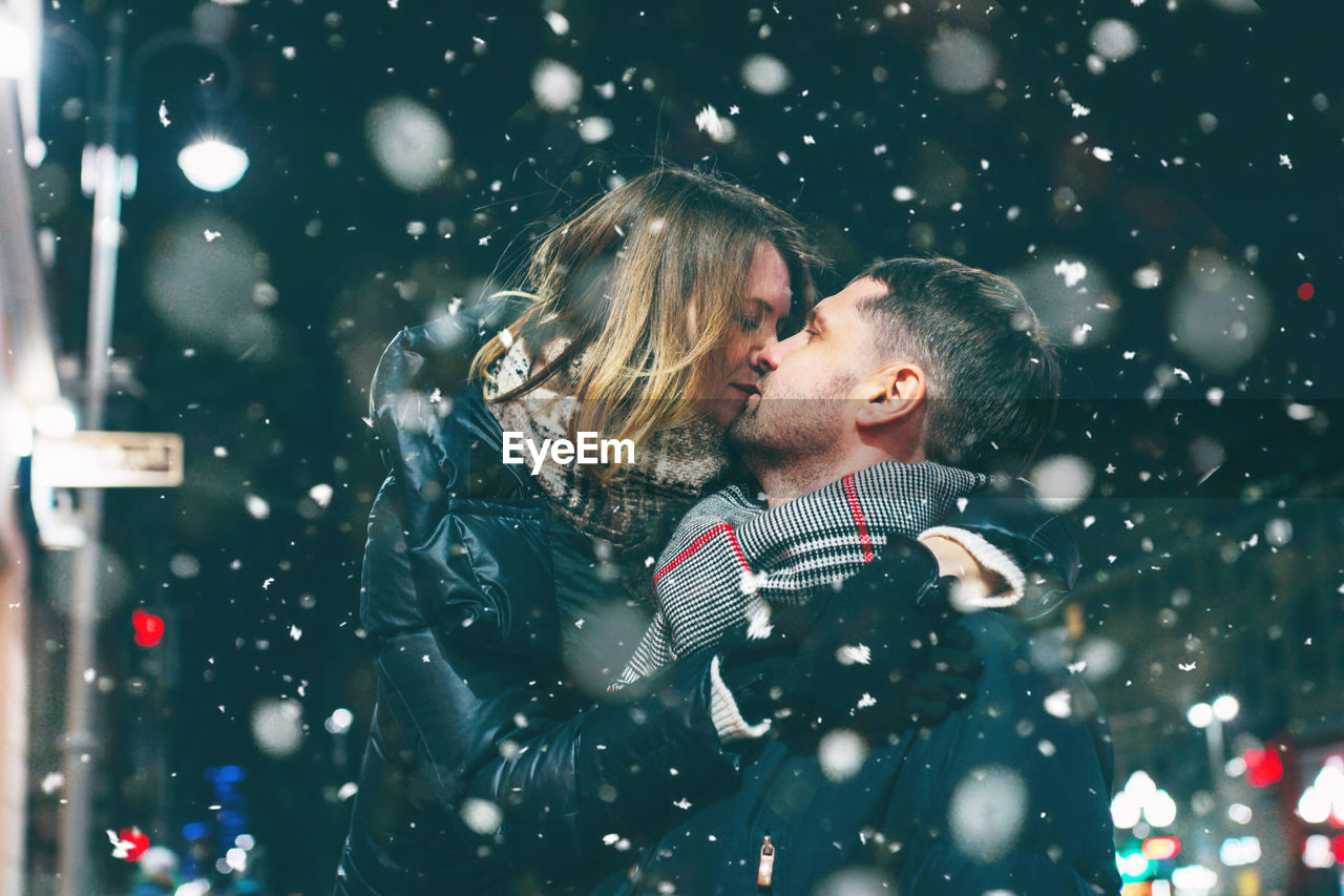Couple Romancing While Standing Against Sky At Night During Snowing