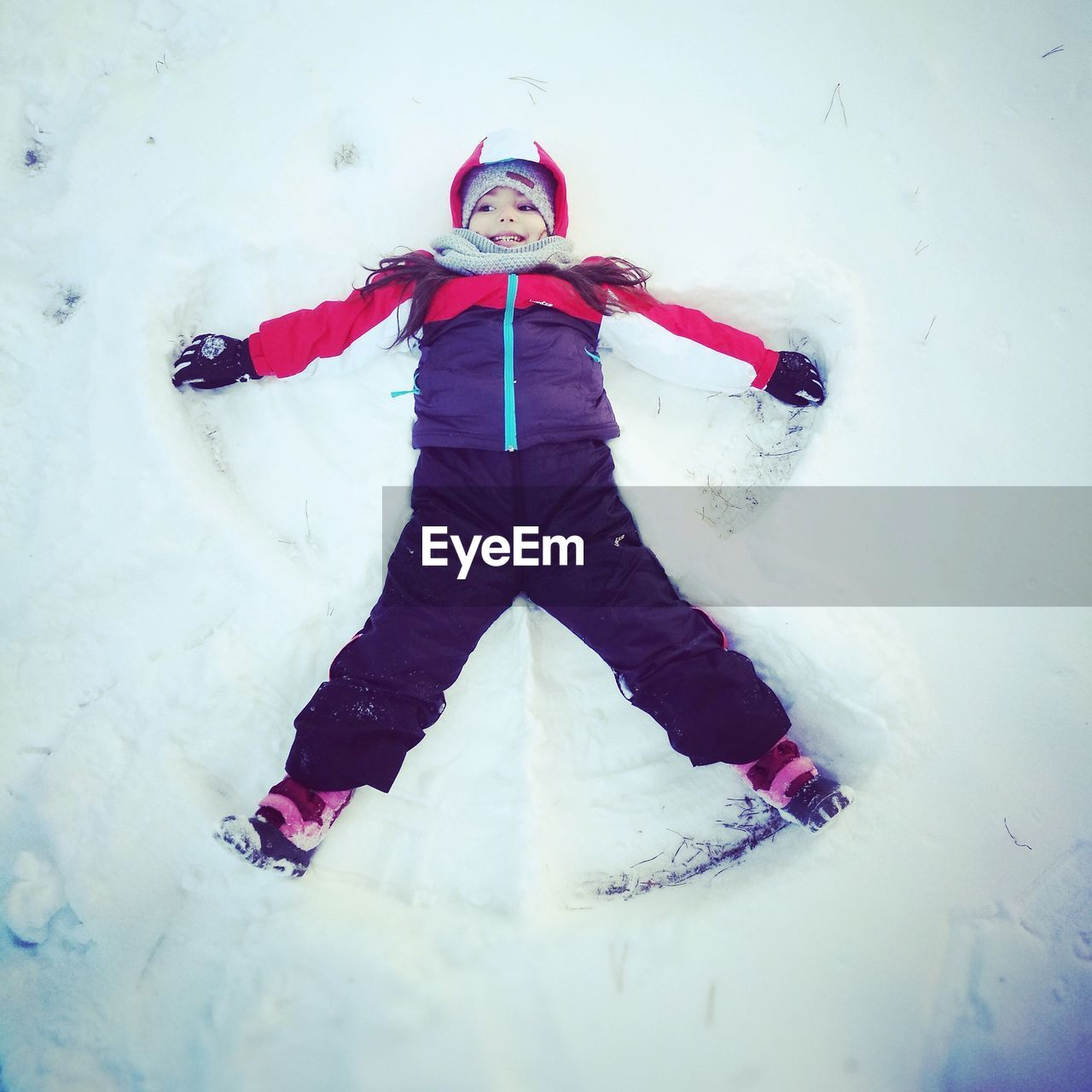 winter, snow, cold temperature, fun, warm clothing, full length, white color, childhood, one person, weather, happiness, knit hat, smiling, front view, enjoyment, playing, leisure activity, real people, lifestyles, outdoors, girls, day, tobogganing, young adult, people