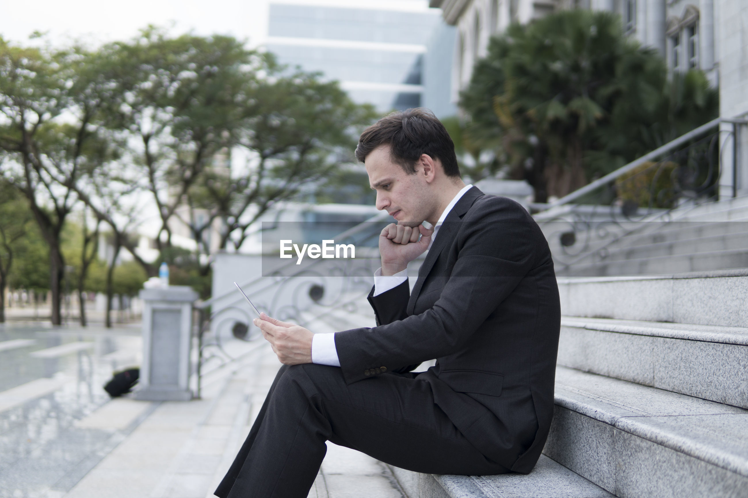 Businessman with laptop sitting on staircase