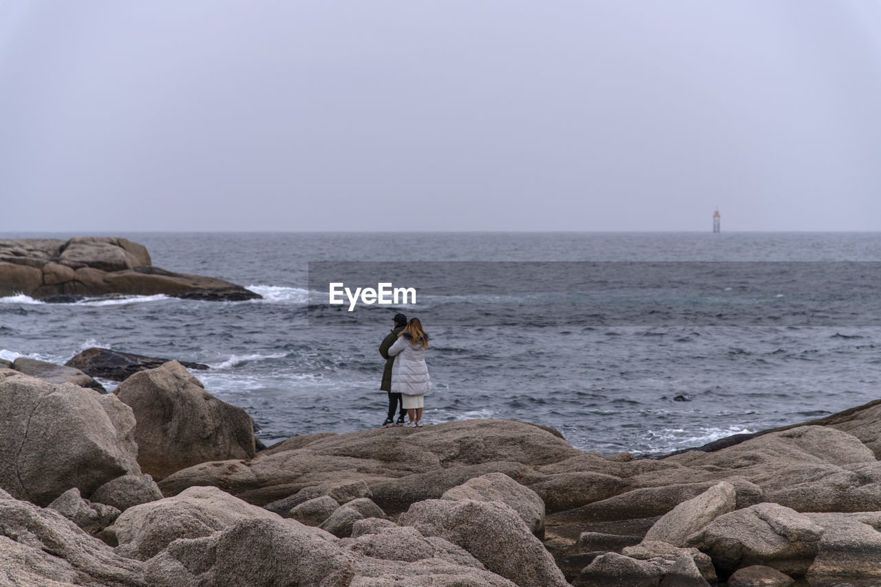 sea, water, rock - object, rock, sky, solid, horizon, horizon over water, scenics - nature, beauty in nature, standing, real people, full length, nature, leisure activity, one person, land, clear sky
