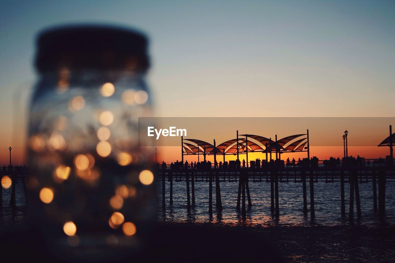 water, sunset, sea, sky, no people, illuminated, outdoors, street light, nature, built structure, beauty in nature, travel destinations, scenics, building exterior, architecture, city, day