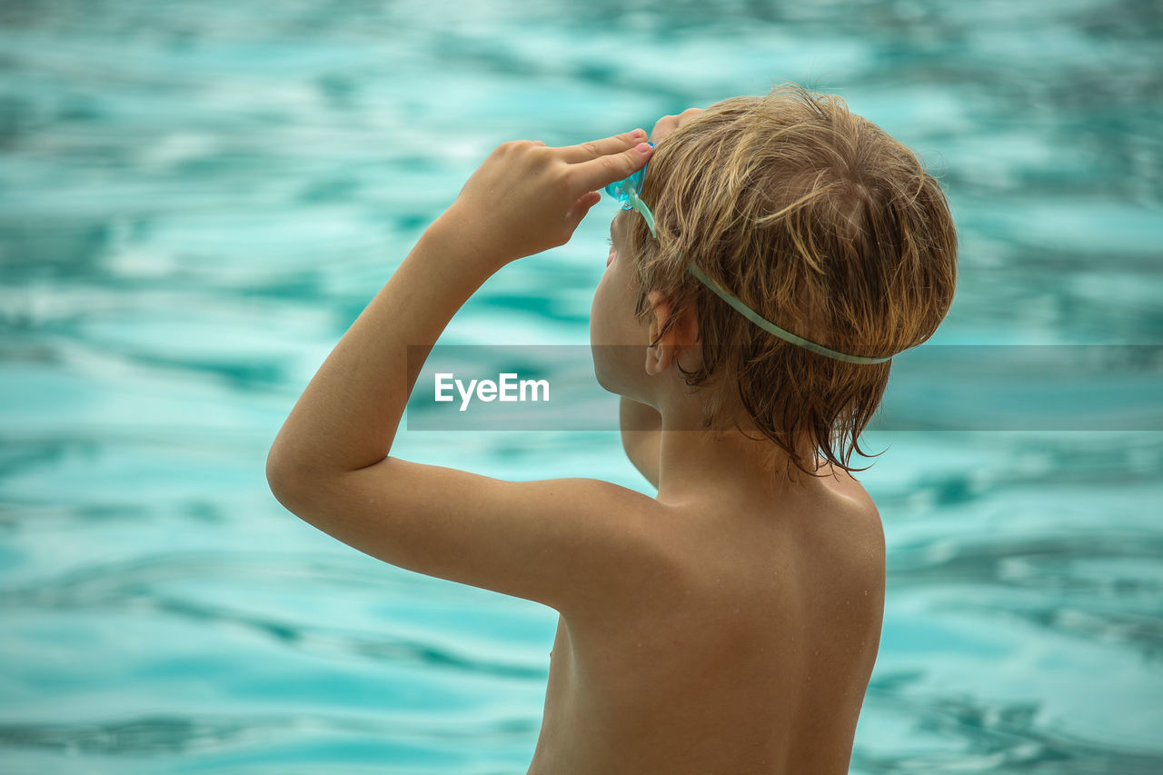 Rear view of shirtless boy wearing swimming goggles while standing by sea