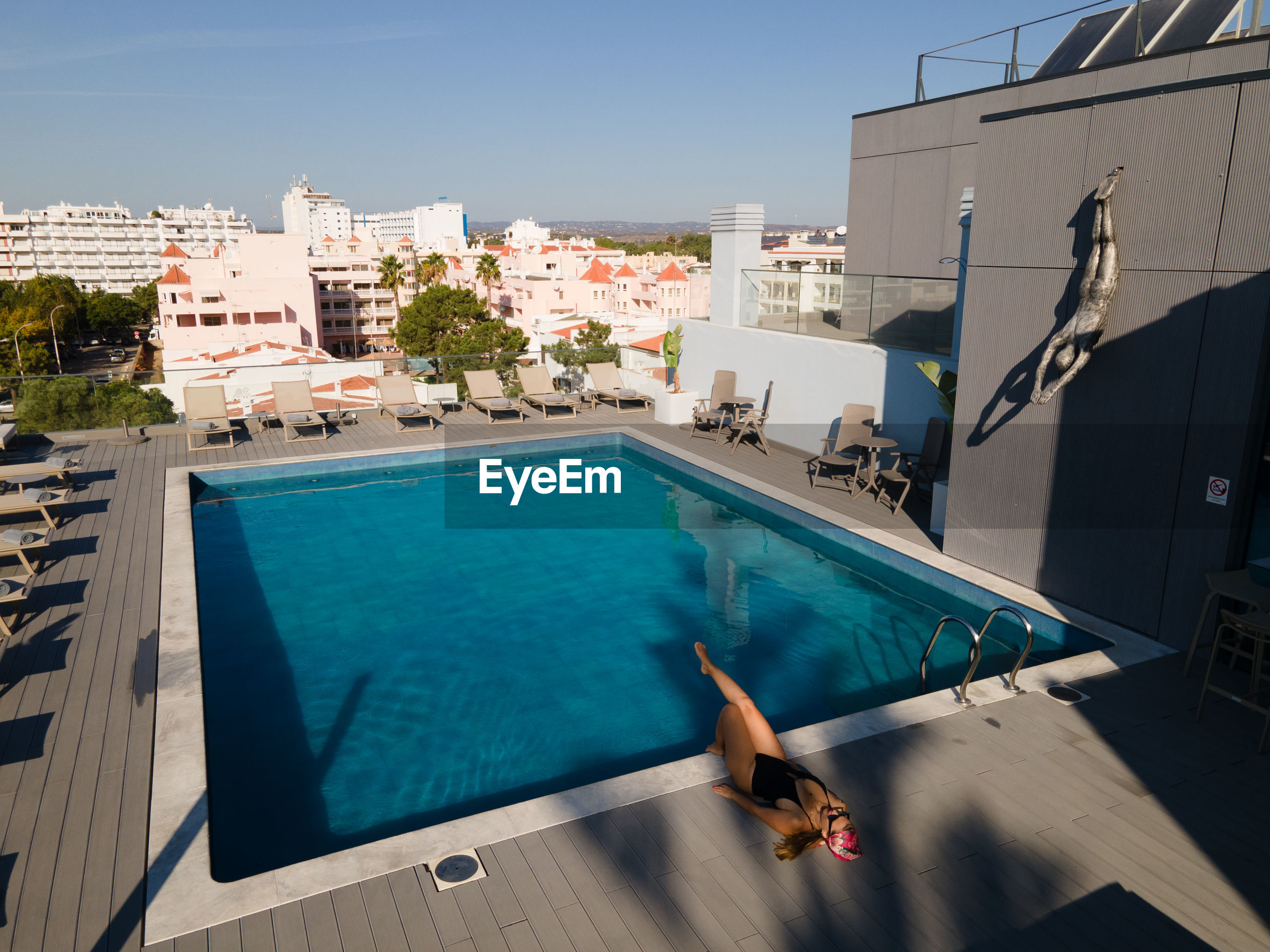 HIGH ANGLE VIEW OF SWIMMING POOL BY BUILDINGS AGAINST BLUE SKY