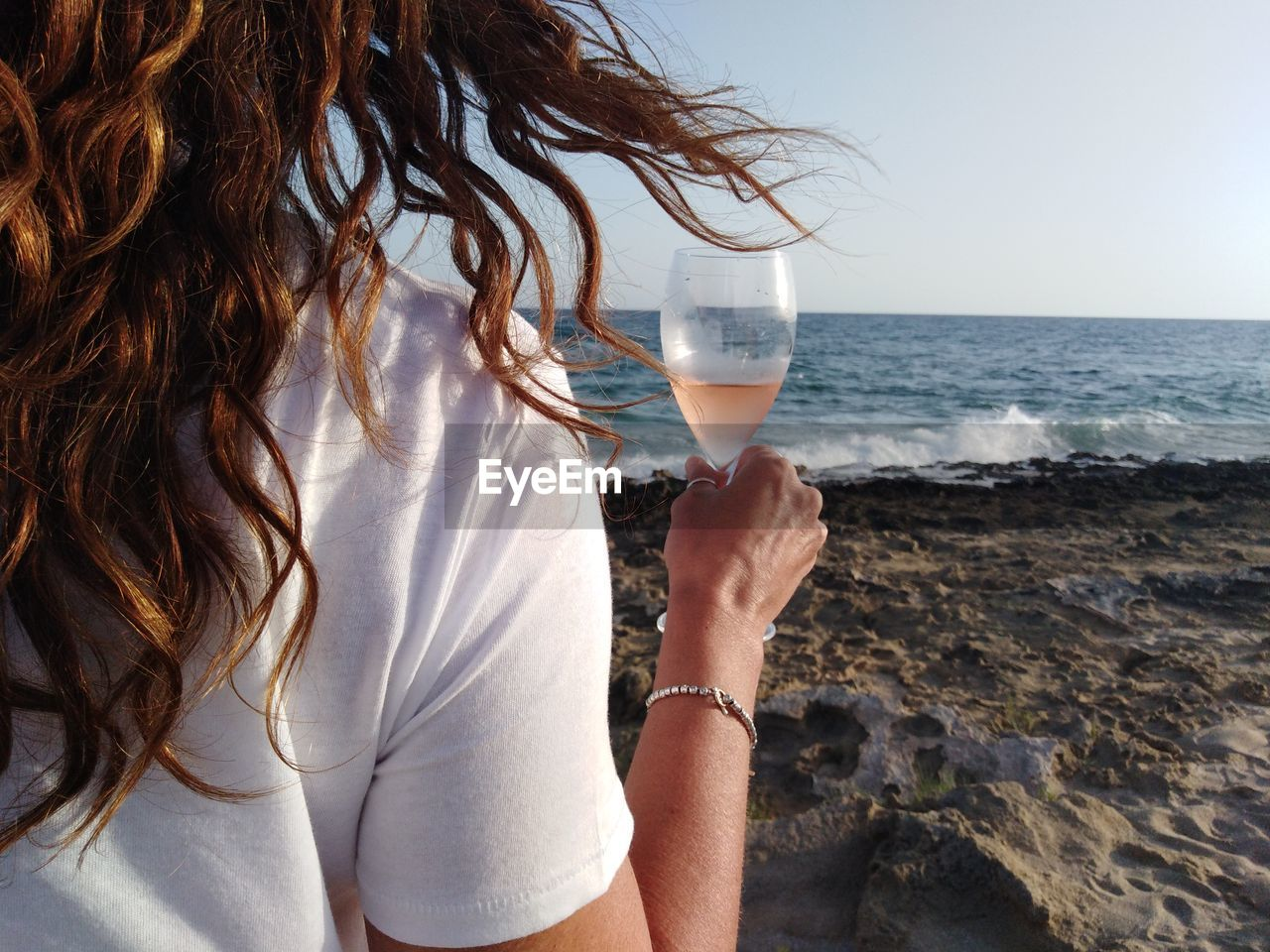 Midsection Of Woman Holding Wineglass While Standing At Beach Against Clear Sky