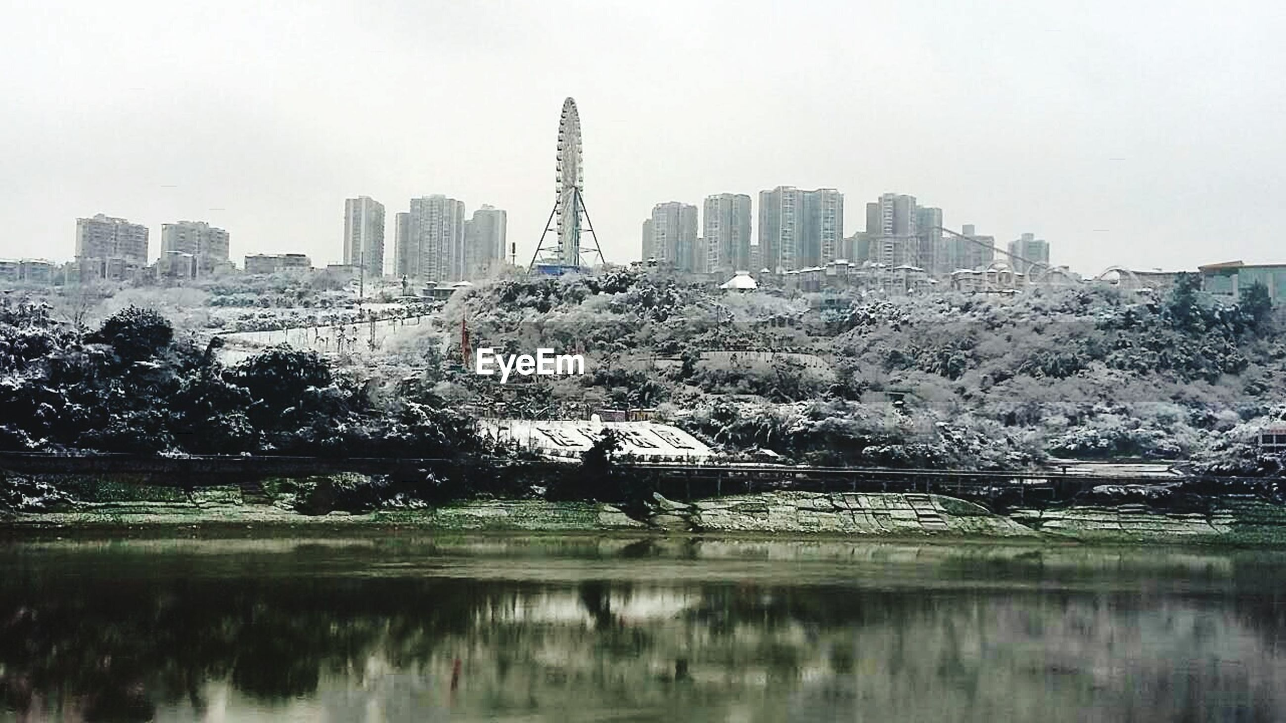 building exterior, architecture, water, city, built structure, skyscraper, winter, waterfront, cold temperature, cityscape, season, snow, river, reflection, weather, lake, modern, urban skyline, sky, office building