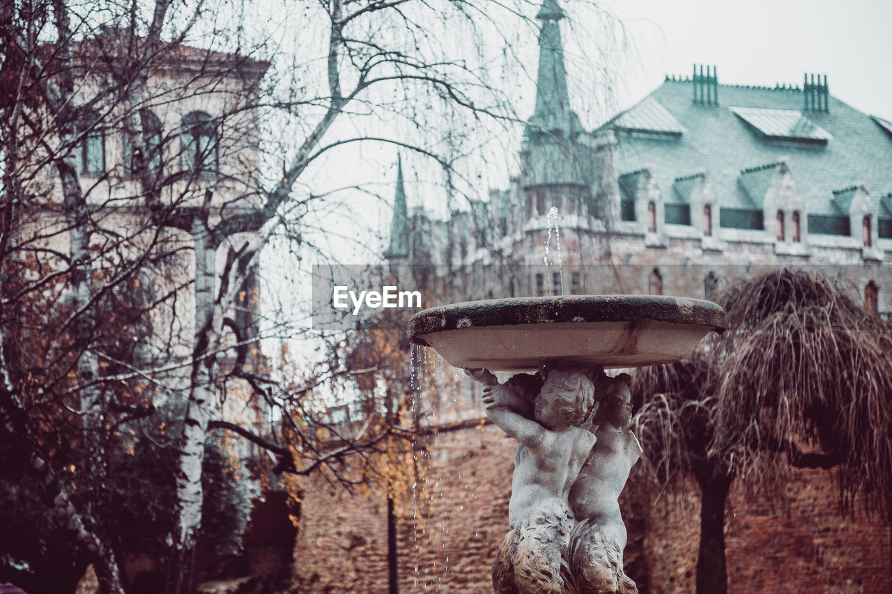 built structure, building exterior, architecture, tree, plant, nature, day, winter, focus on foreground, building, bare tree, cold temperature, representation, sculpture, human representation, statue, water, snow, city, outdoors, rain, snowing, warm clothing