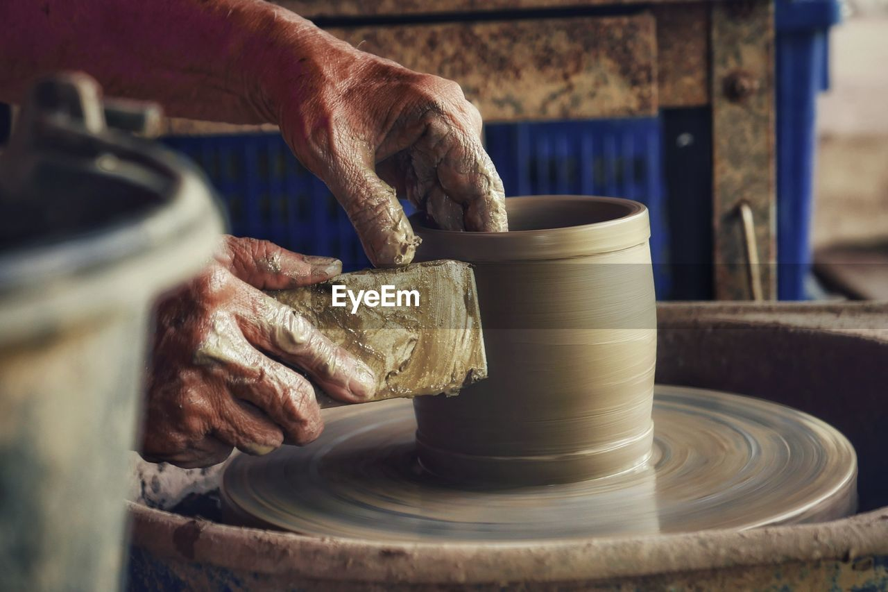 Cropped Hands Of Potter Using Pottery Wheel In Workshop