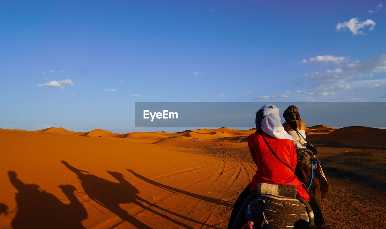 sky, real people, leisure activity, lifestyles, desert, beauty in nature, scenics - nature, landscape, nature, rear view, people, adult, non-urban scene, land, cloud - sky, women, sunlight, environment, two people, travel, arid climate, climate, outdoors, riding
