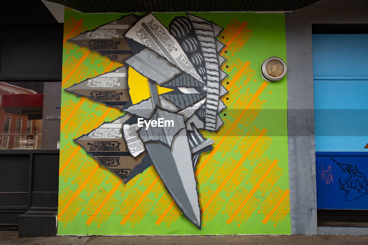 multi colored, creativity, yellow, art and craft, no people, wall - building feature, graffiti, architecture, day, close-up, built structure, communication, text, mural, outdoors, building exterior, western script, paper, craft