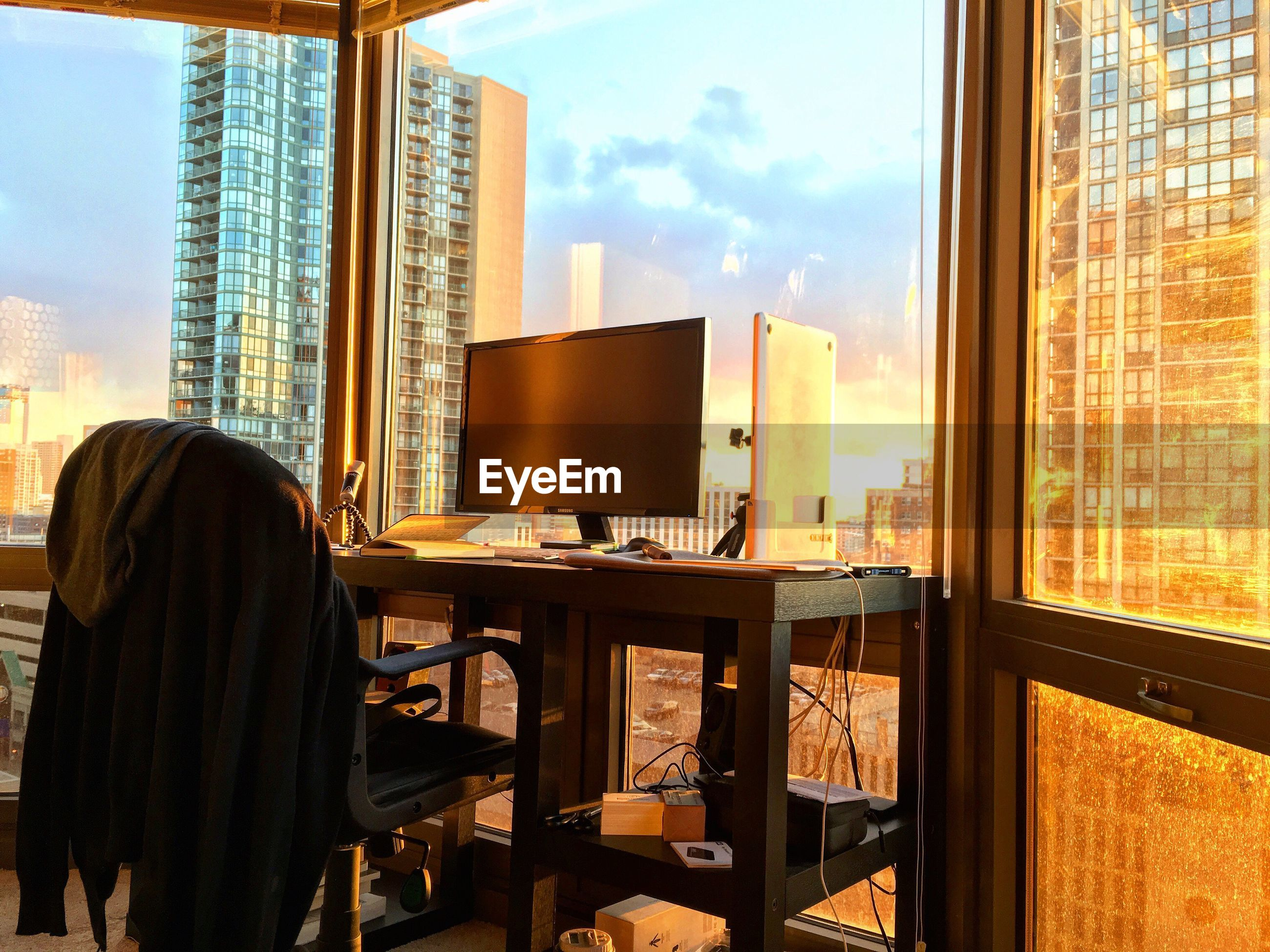 Computer on desk in office against modern building during sunset