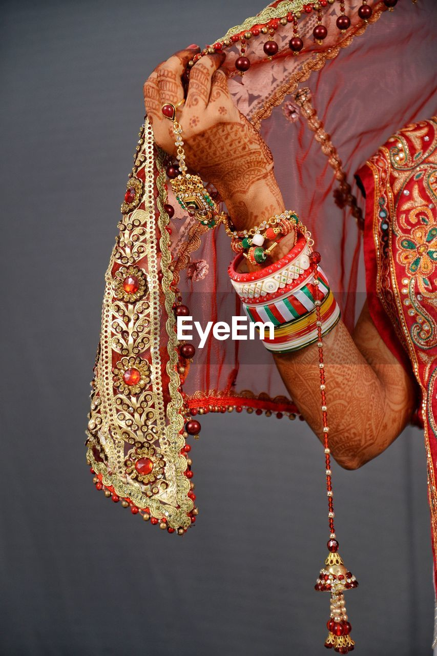 Midsection of bride in traditional clothing over gray background