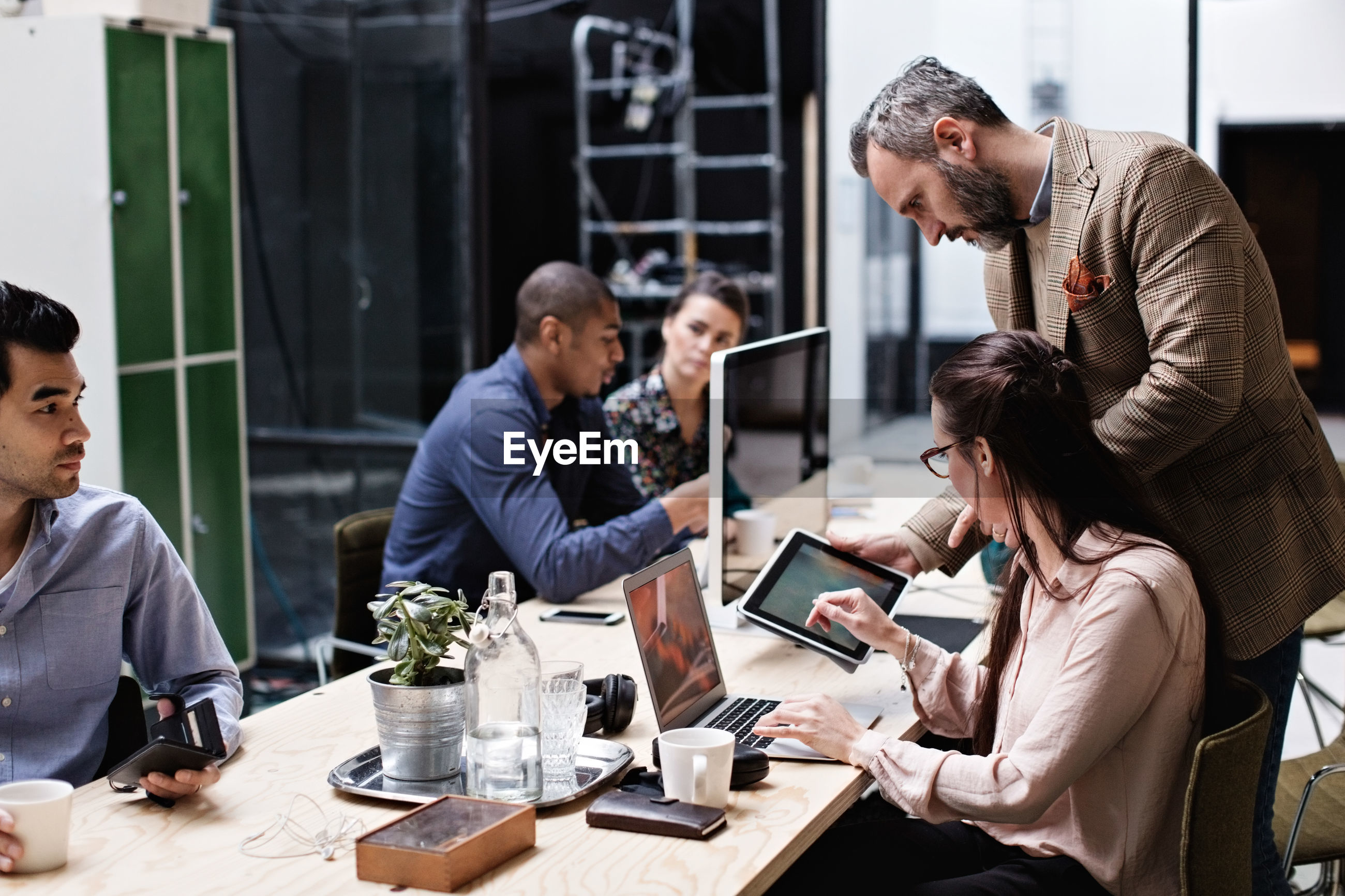 Businessman discussing over digital tablet with colleagues in office meeting