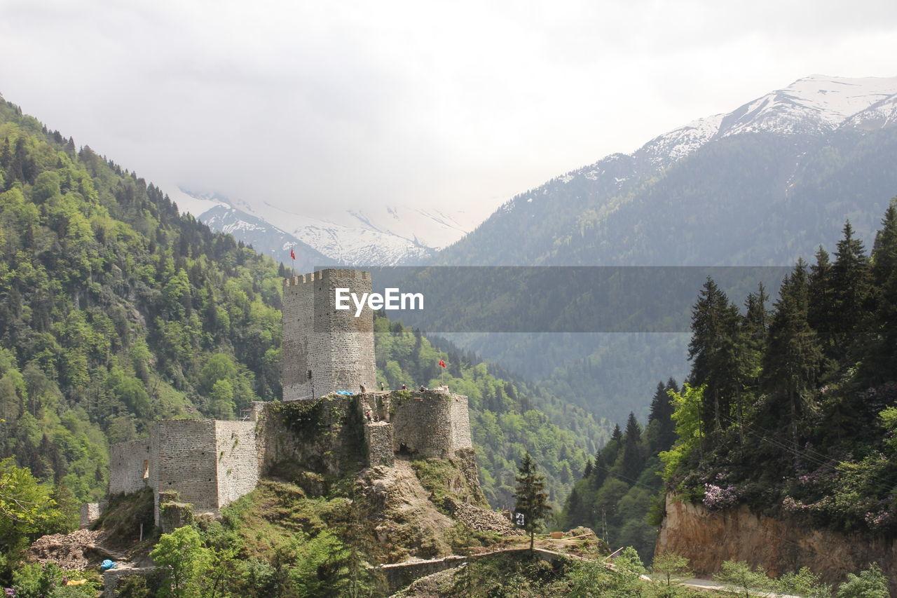 BUILT STRUCTURE ON LANDSCAPE AGAINST MOUNTAINS