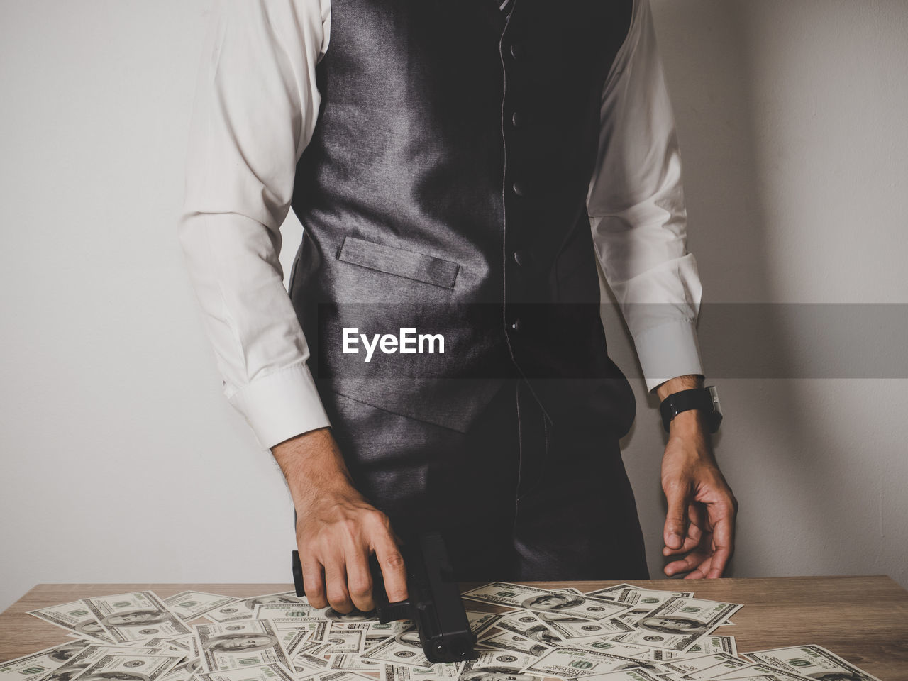Midsection Of Businessman By Paper Currencies Holding Gun