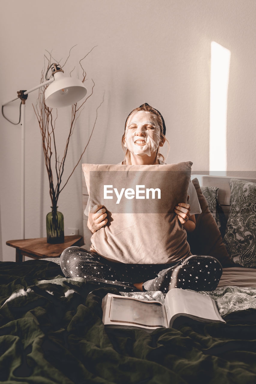 Woman with face mask holding cushion while sitting on bed at home