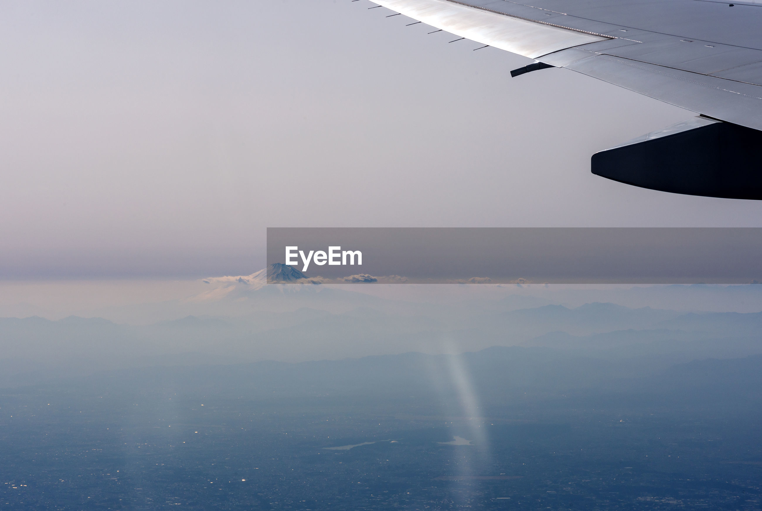 Airplane flying over fuji mountain against sky