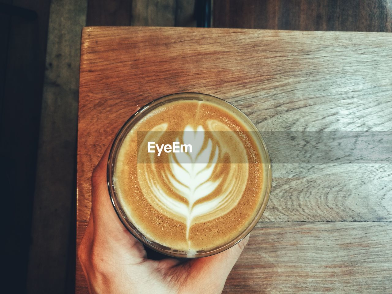 human hand, drink, frothy drink, refreshment, table, food and drink, indoors, one person, froth art, coffee - drink, real people, cappuccino, human body part, close-up, day, freshness, people