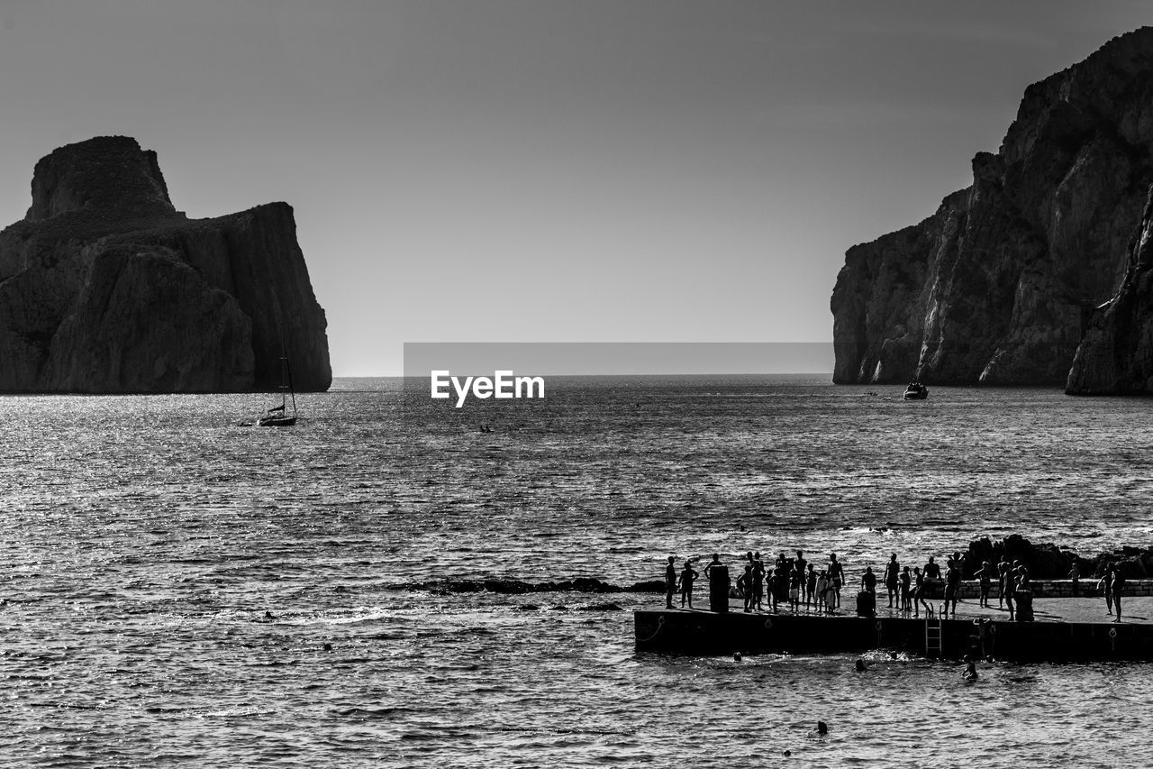 water, sea, sky, beauty in nature, waterfront, rock, scenics - nature, horizon over water, rock formation, rock - object, horizon, nature, solid, clear sky, day, nautical vessel, transportation, tranquility, land, outdoors, no people, stack rock