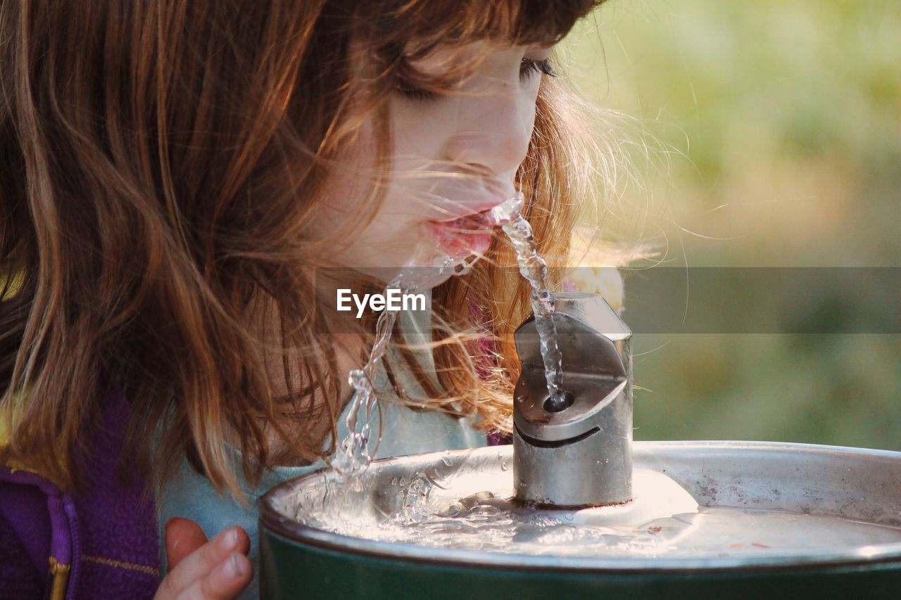 Close-up of girl drinking water from fountain