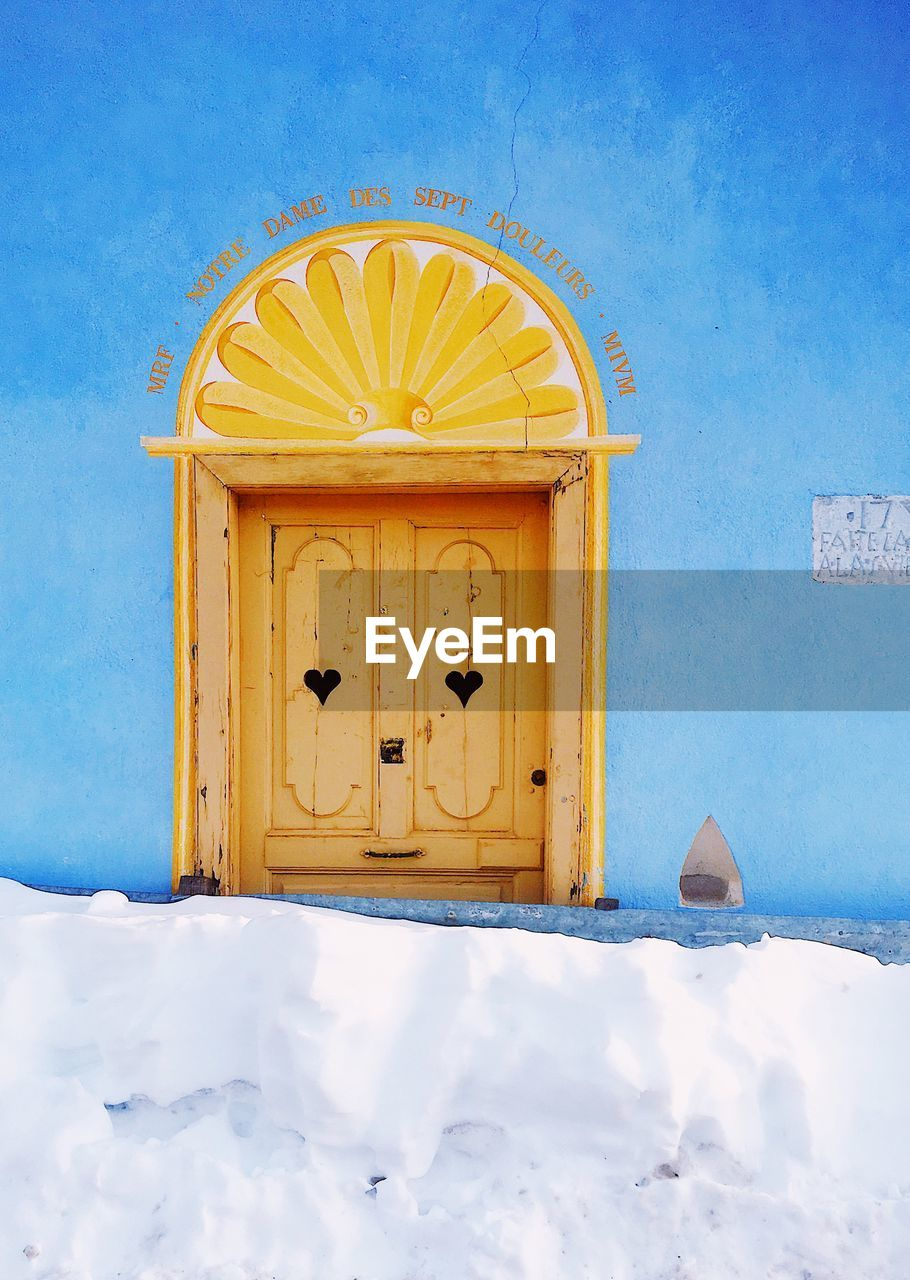 architecture, built structure, door, entrance, building exterior, blue, building, no people, yellow, nature, snow, sky, day, text, house, cold temperature, wall - building feature, outdoors, communication, sunlight