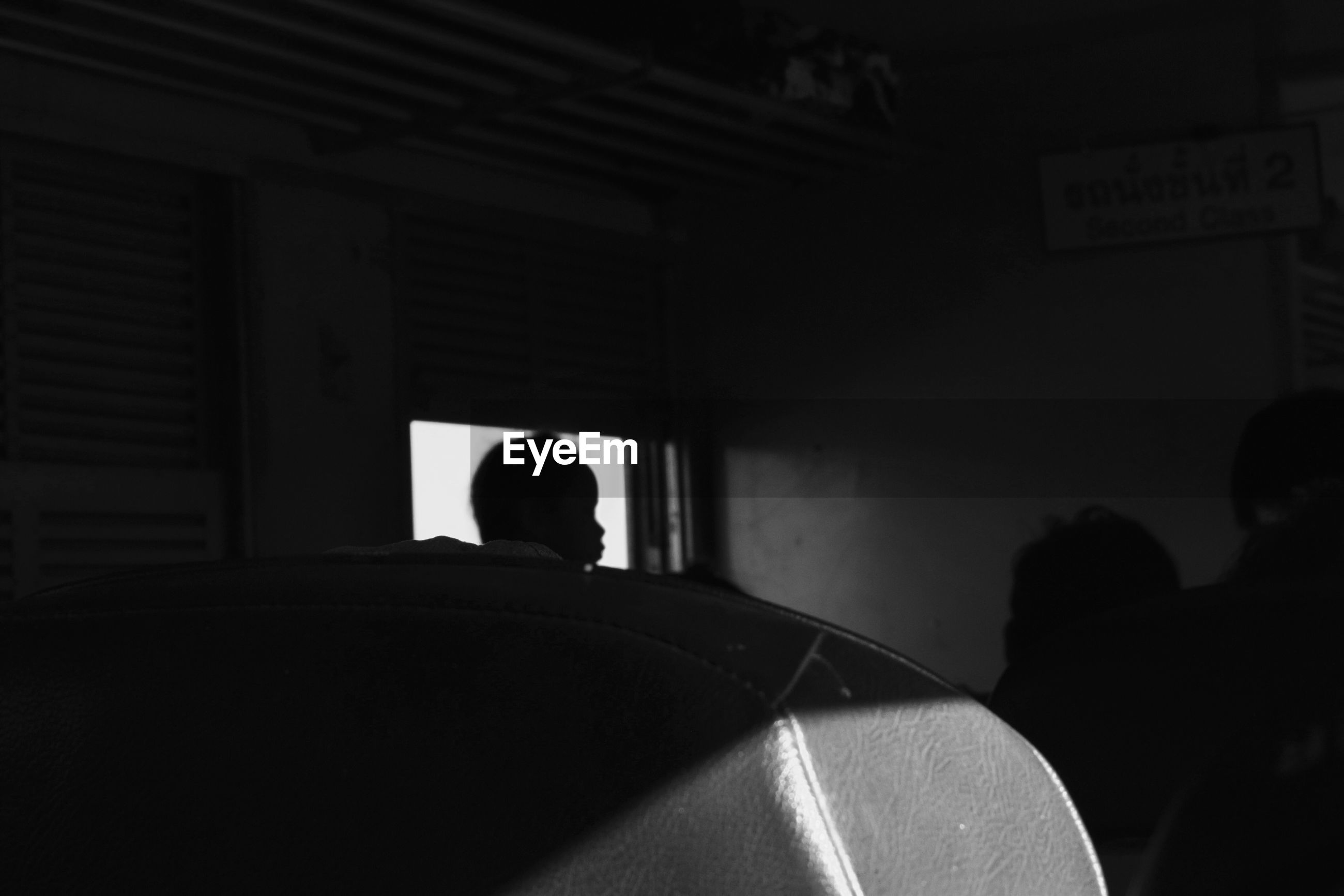 REAR VIEW OF SILHOUETTE PERSON SITTING IN TRAIN