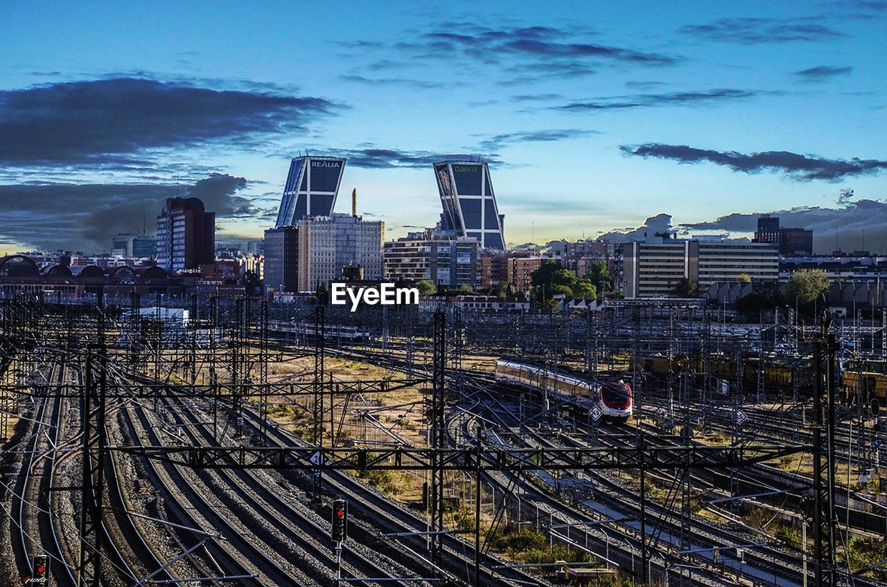 architecture, skyscraper, built structure, city, transportation, building exterior, train - vehicle, rail transportation, railroad track, sky, high angle view, public transportation, no people, cityscape, modern, outdoors, day, urban skyline