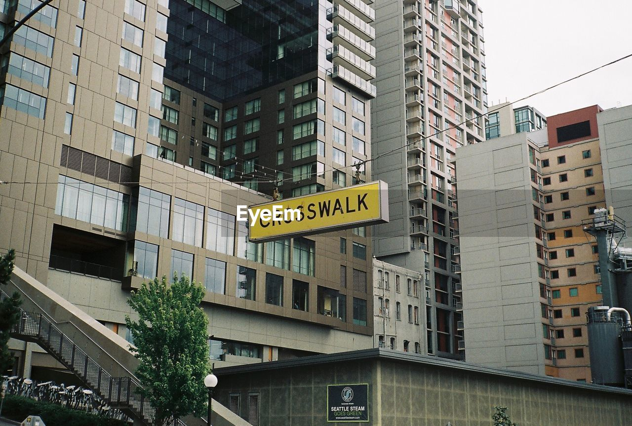 Low Angle View Of Information Sign Against Modern Buildings