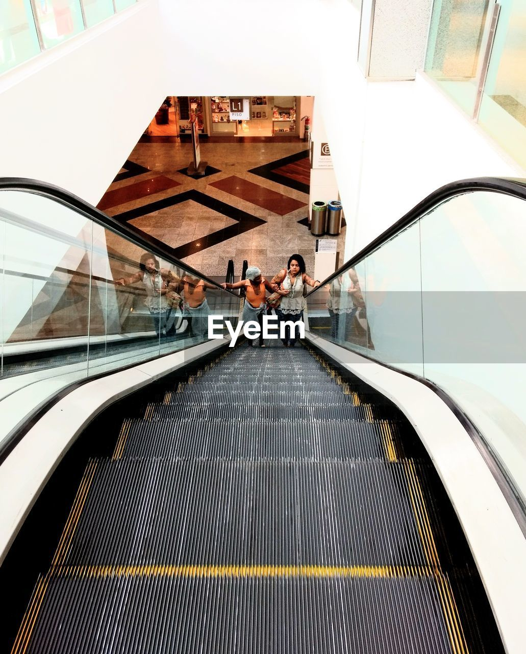 architecture, staircase, escalator, real people, transportation, men, railing, steps and staircases, built structure, lifestyles, connection, adult, convenience, women, group of people, leisure activity, indoors, moving walkway, travel, modern, couple - relationship