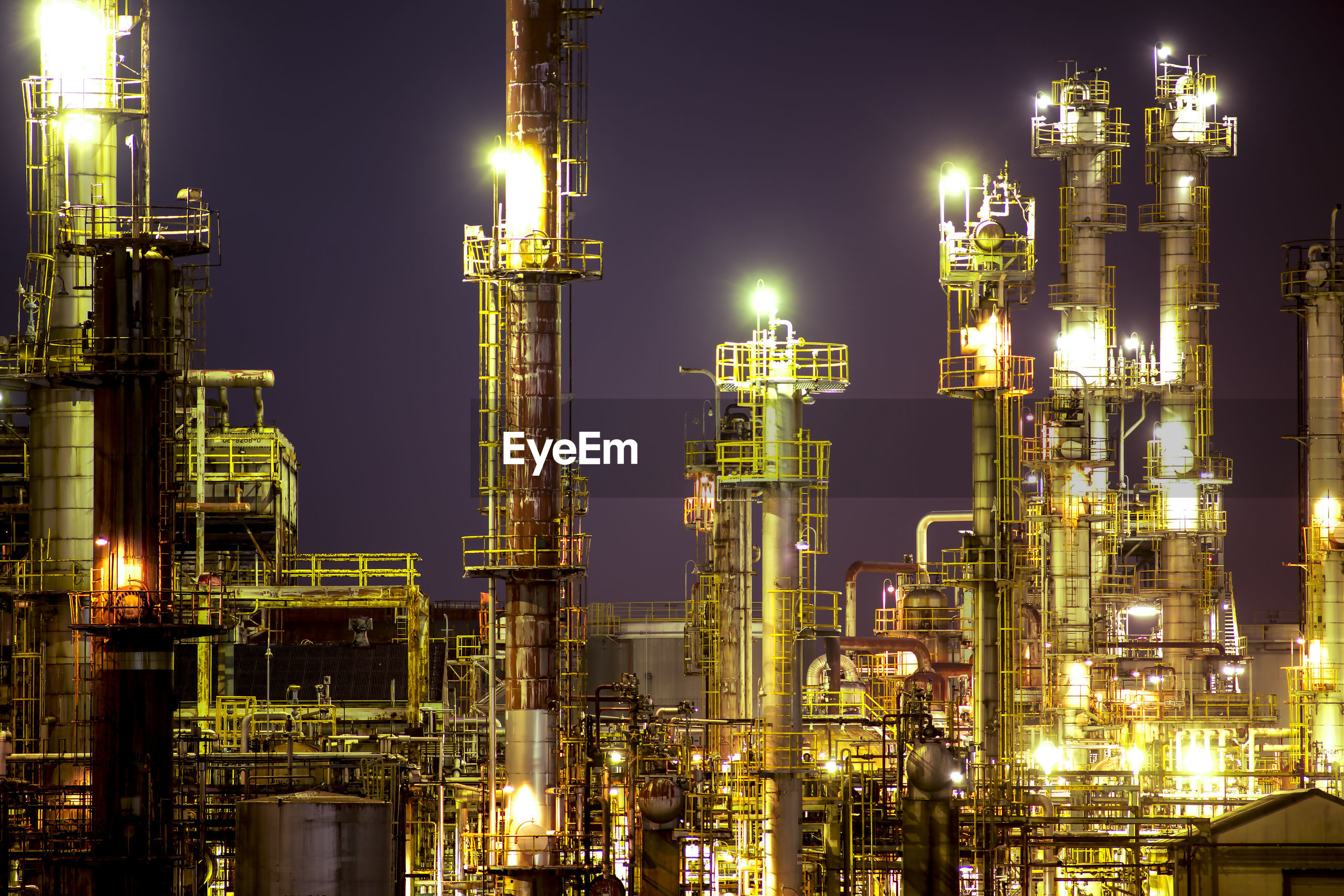 Low angle view of illuminated oil industry against sky at night