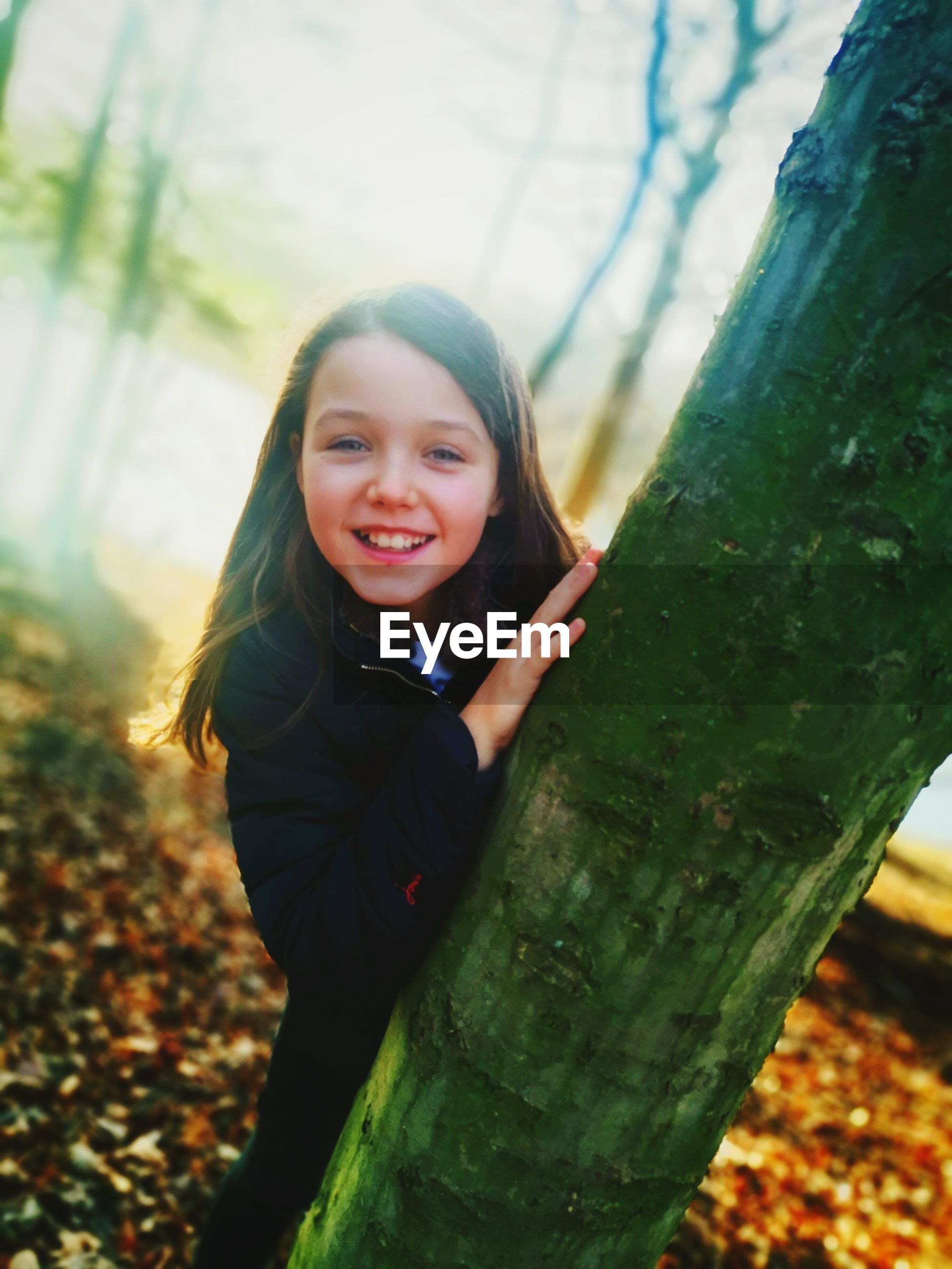 PORTRAIT OF HAPPY GIRL SMILING AGAINST TREE