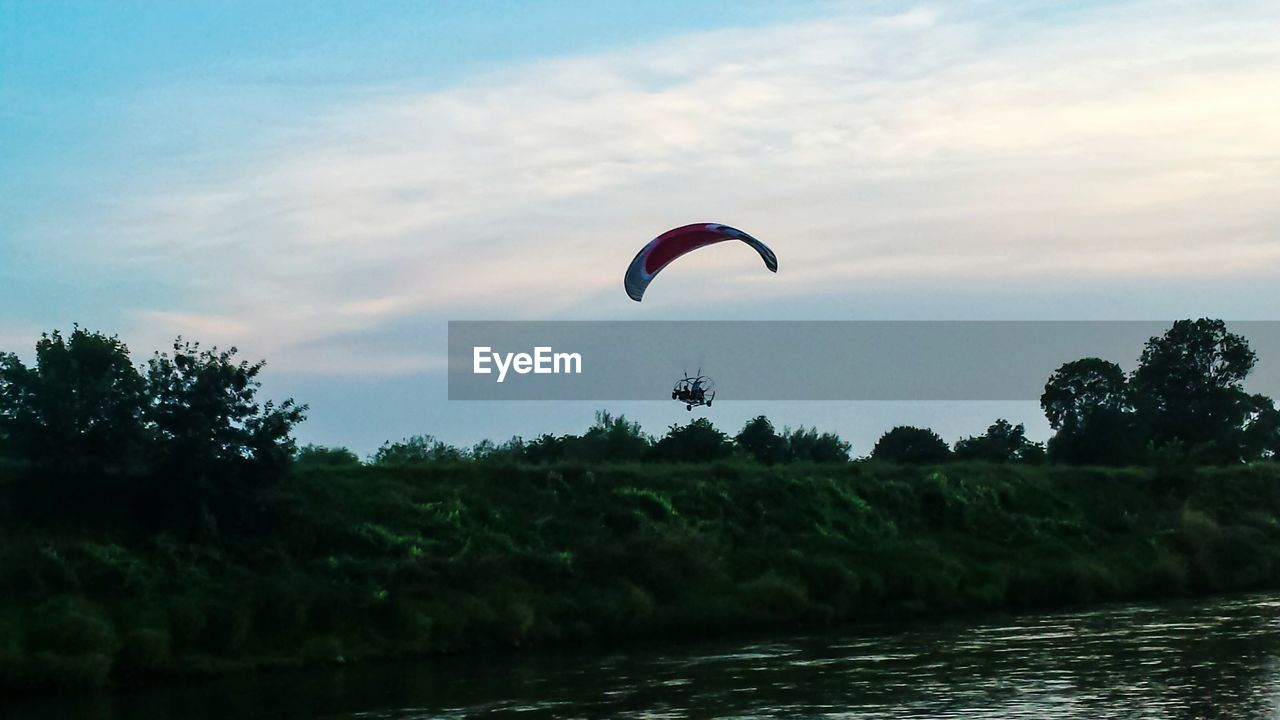adventure, parachute, sky, mid-air, extreme sports, real people, tree, leisure activity, nature, one person, paragliding, outdoors, water, lifestyles, flying, day, sunset, sport, beauty in nature, scenics, people