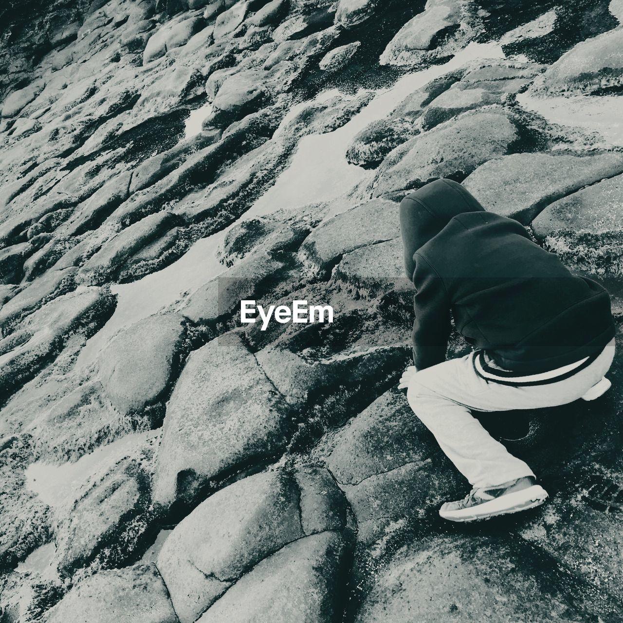 High angle view of boy playing on rocks