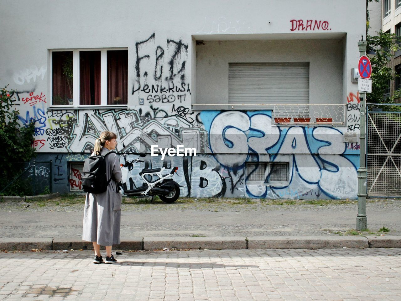 graffiti, building exterior, text, architecture, full length, built structure, outdoors, communication, day, one person, casual clothing, real people, people