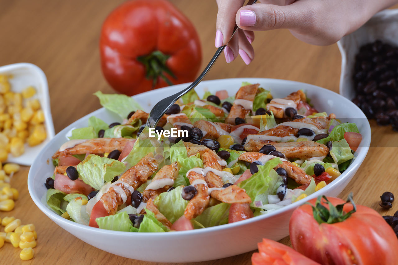 Close-Up Of Hand Holding Salad In Bowl