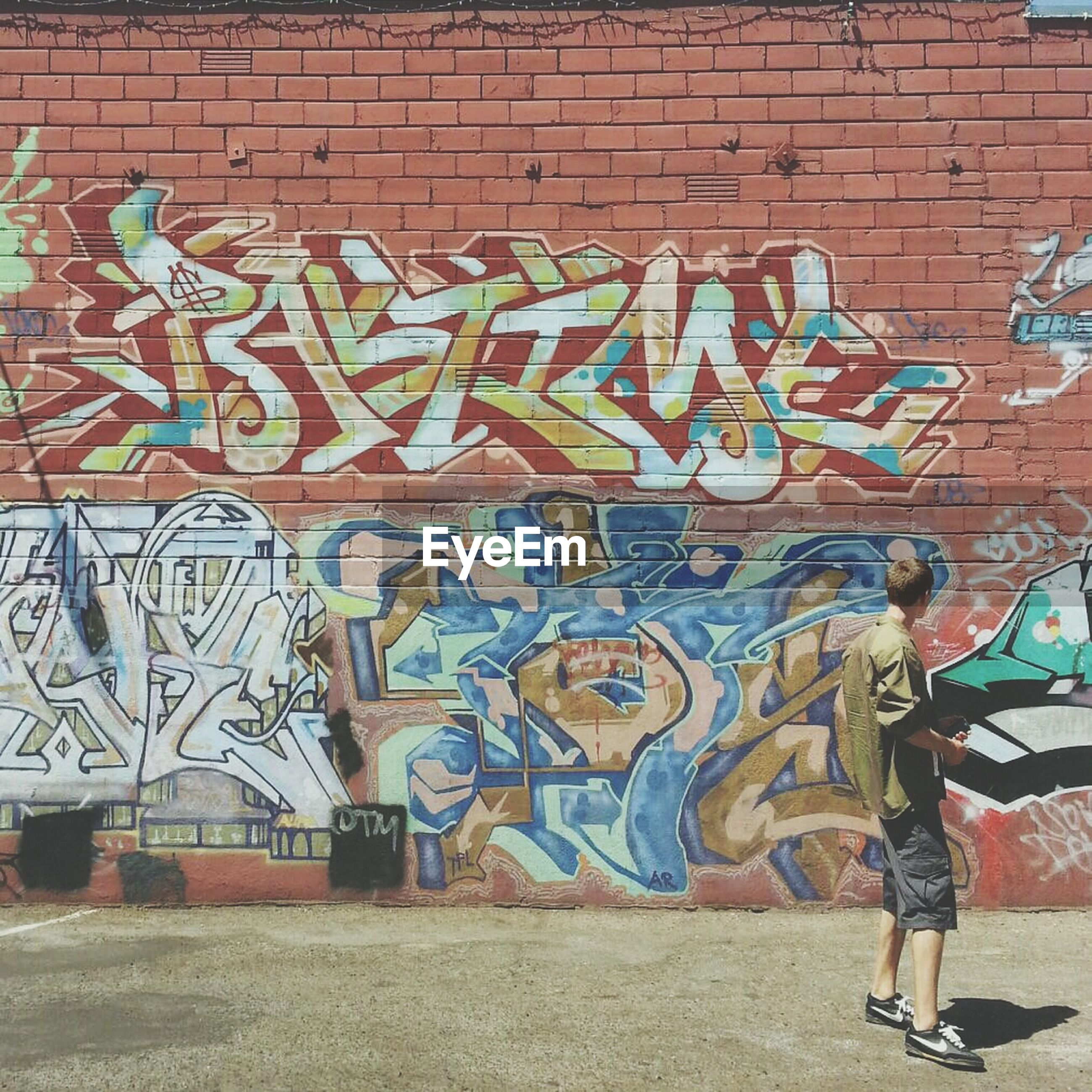 graffiti, art, art and craft, wall - building feature, creativity, built structure, architecture, building exterior, lifestyles, full length, street art, wall, leisure activity, text, casual clothing, brick wall, men, standing