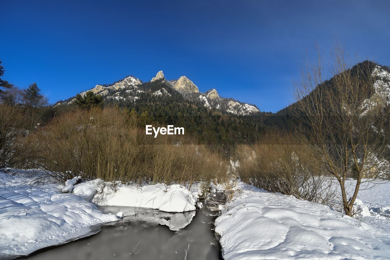 winter, cold temperature, sky, beauty in nature, tranquil scene, scenics - nature, snow, tranquility, nature, mountain, environment, no people, water, day, non-urban scene, clear sky, blue, landscape, frozen, ice, outdoors, snowcapped mountain, mountain peak, flowing water