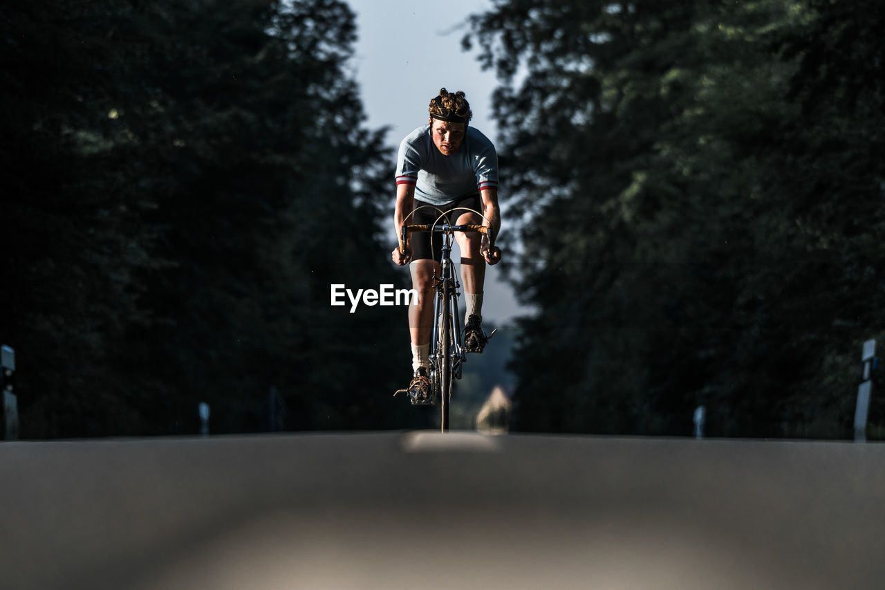 Young Man Riding Bicycle On Road