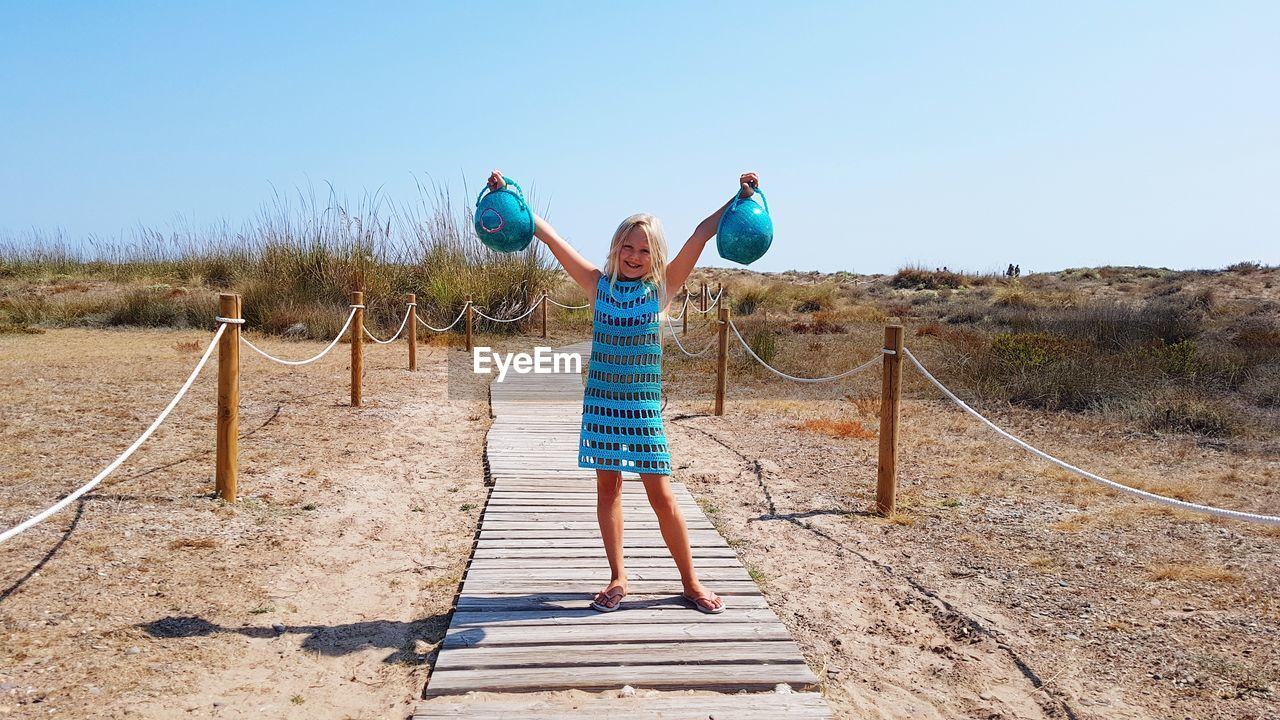 Girl holding baskets while standing on boardwalk at beach
