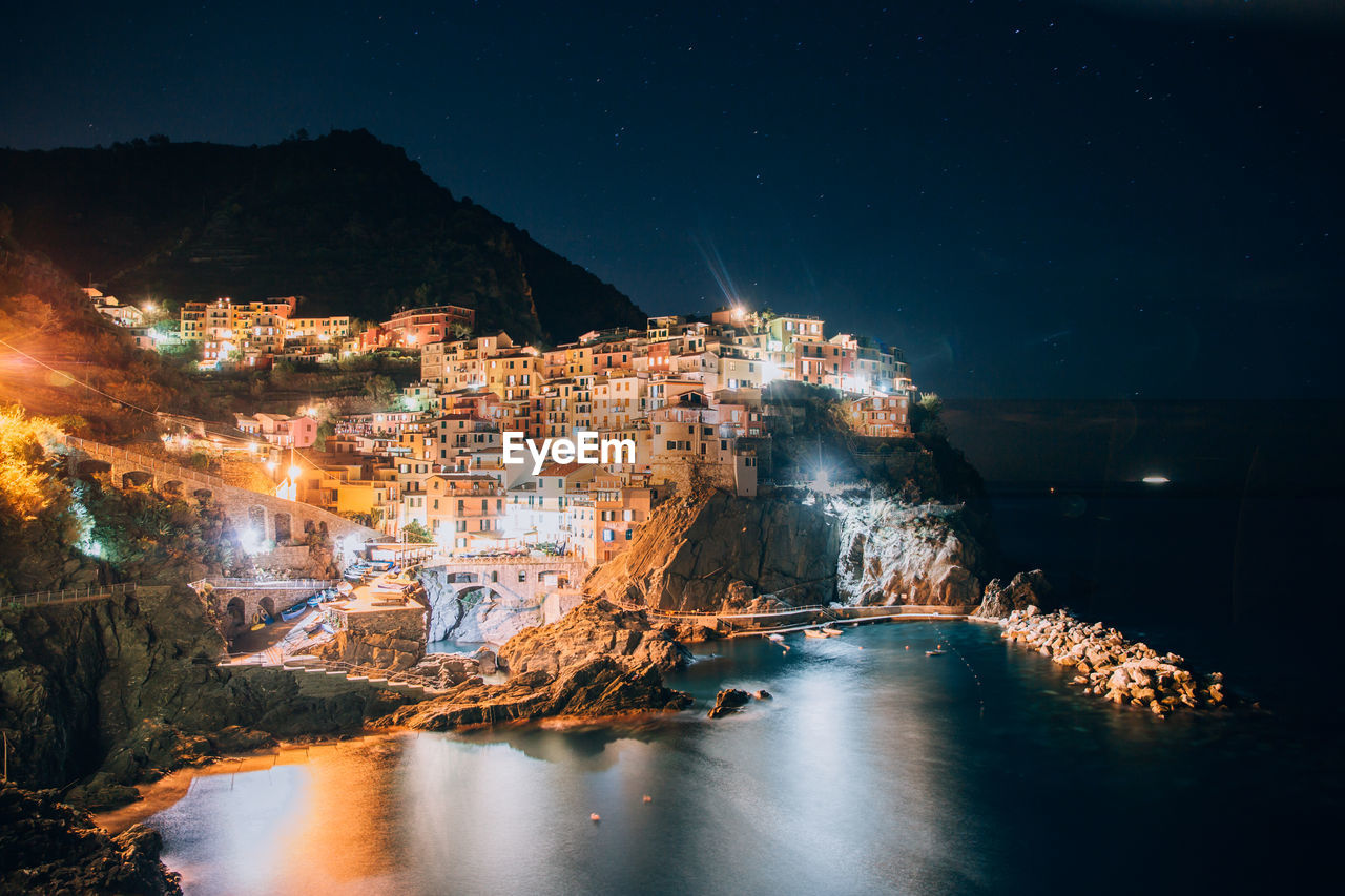 Illuminated Houses On Cliff By Sea At Night