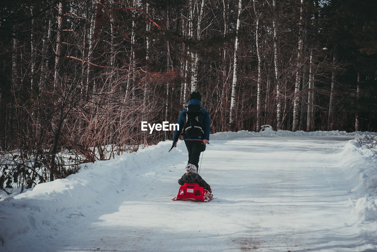 Rear view of woman with son walking on snow covered road