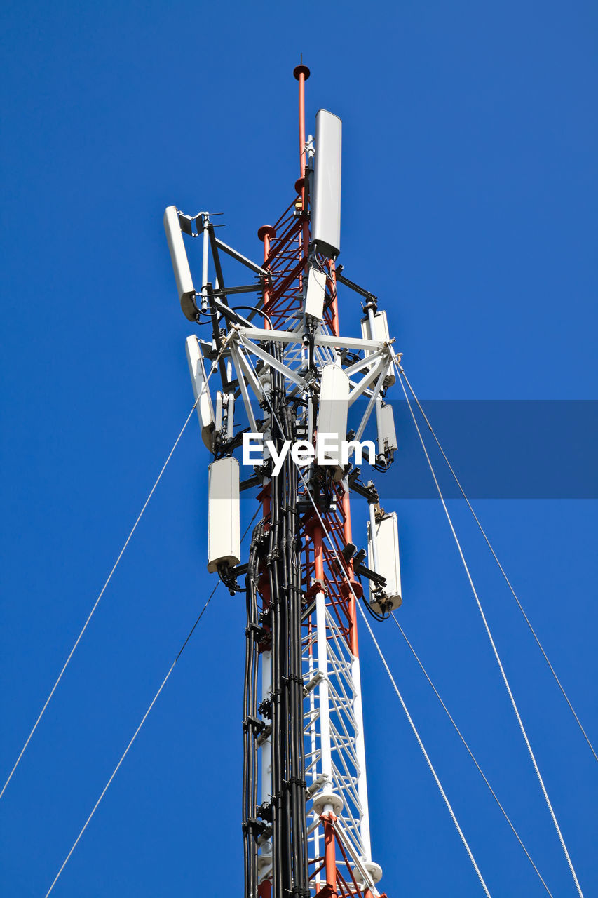 sky, low angle view, blue, clear sky, technology, day, nature, no people, metal, fuel and power generation, cable, connection, communication, sunlight, outdoors, power supply, tower, built structure, tall - high, electricity, vapor trail, global communications, electrical equipment