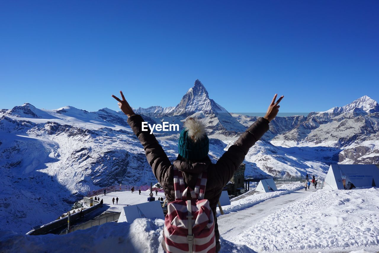 Woman In Snow Covered Mountain Against Clear Blue Sky