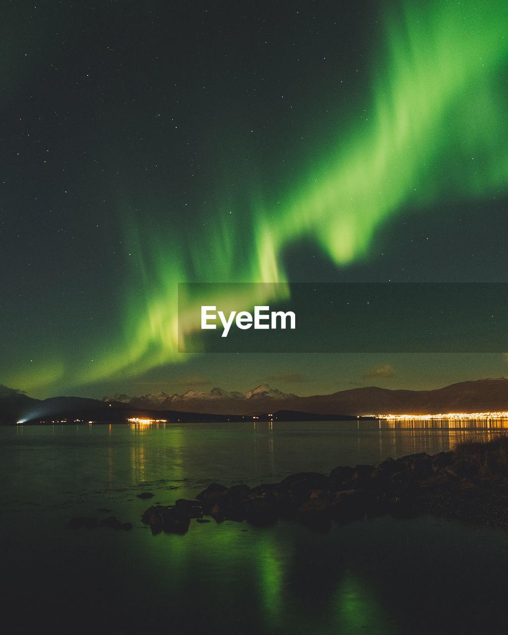 Aurora polaris over lake against sky at night