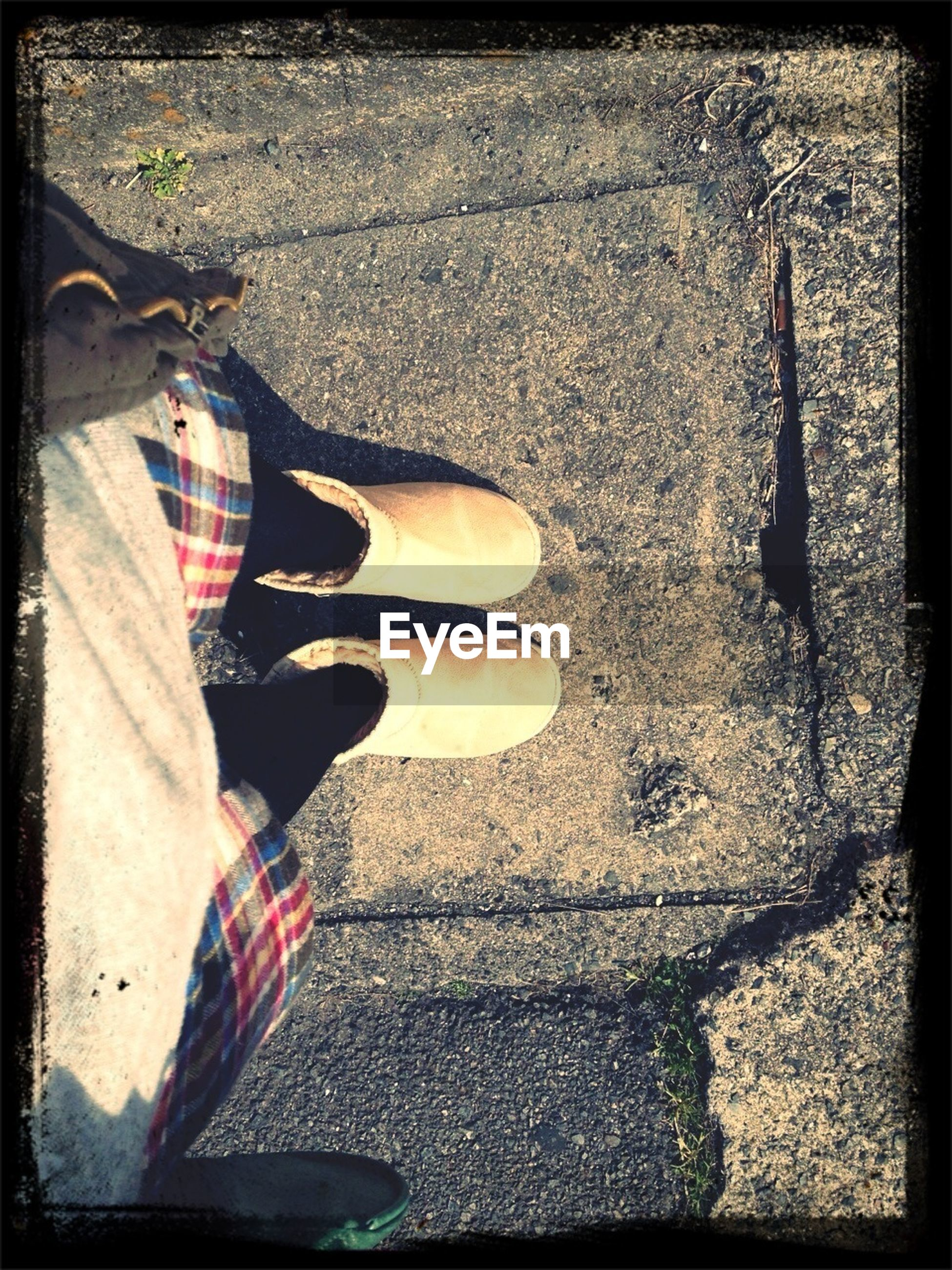 low section, shoe, person, transfer print, high angle view, auto post production filter, footwear, personal perspective, human foot, street, transportation, standing, canvas shoe, part of, lifestyles, pair, jeans
