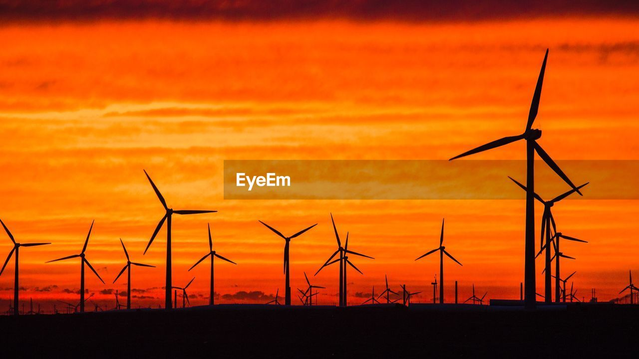 Silhouette wind turbines on land against dramatic sky during sunset