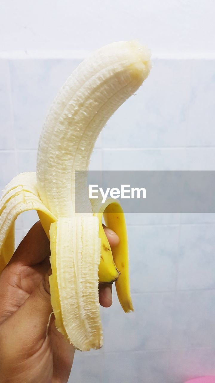 Cropped hand holding banana against white wall