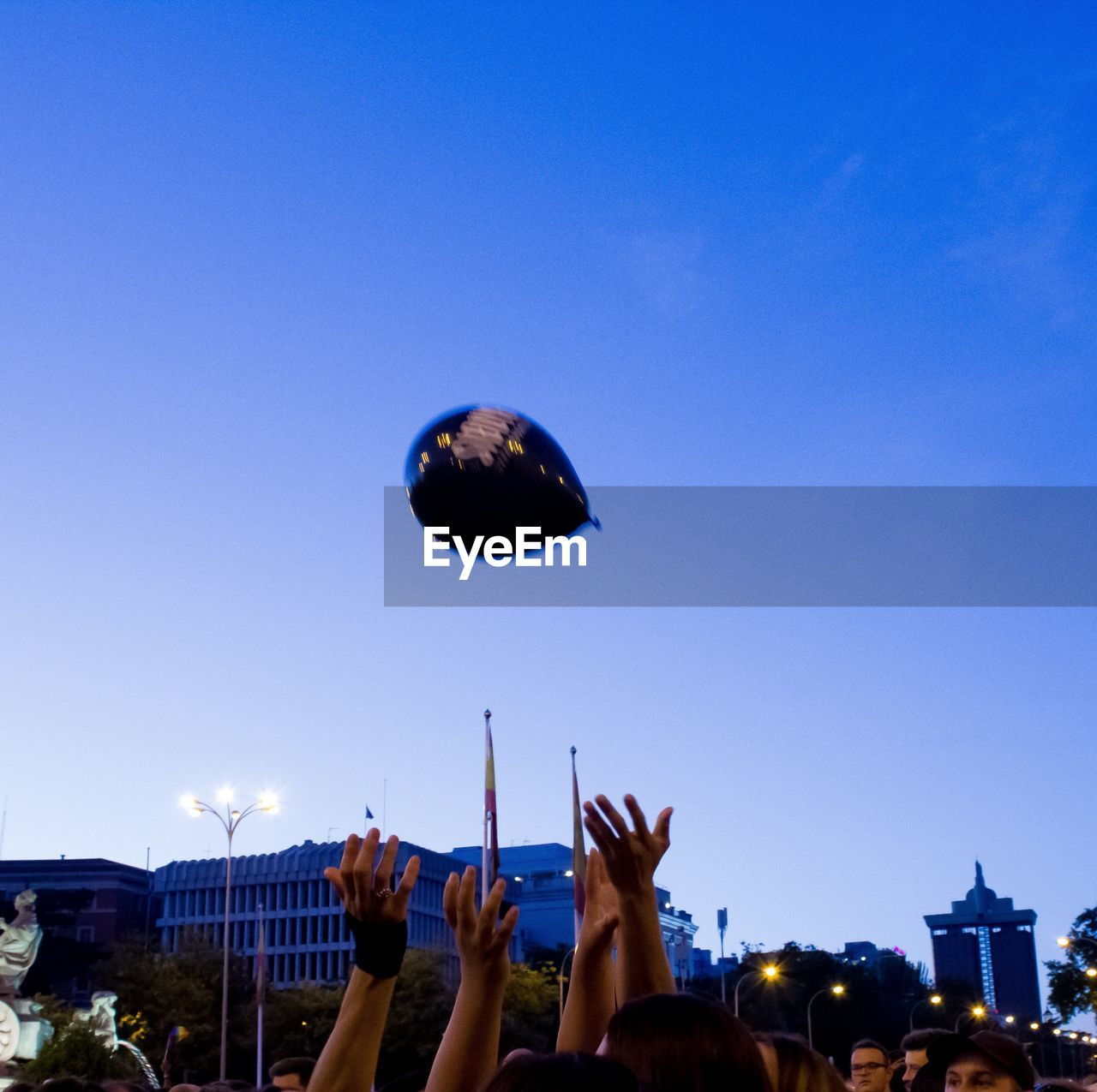 sky, real people, human hand, architecture, hand, built structure, group of people, building exterior, nature, lifestyles, people, human body part, clear sky, blue, copy space, crowd, leisure activity, men, low angle view, women, outdoors, finger, arms raised