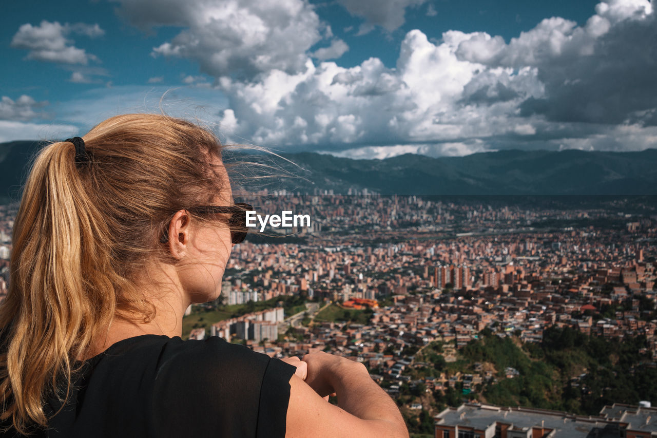 Woman looking at city buildings against cloudy sky