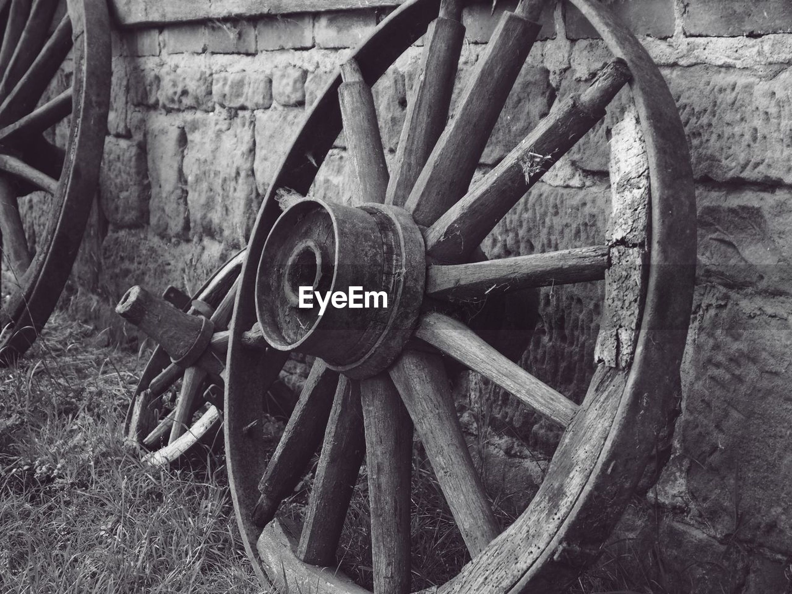 wheel, wagon wheel, old, wood - material, no people, transportation, cart, day, obsolete, close-up, metal, outdoors, wall - building feature, abandoned, field, circle, geometric shape, mode of transportation, run-down, deterioration, spoke