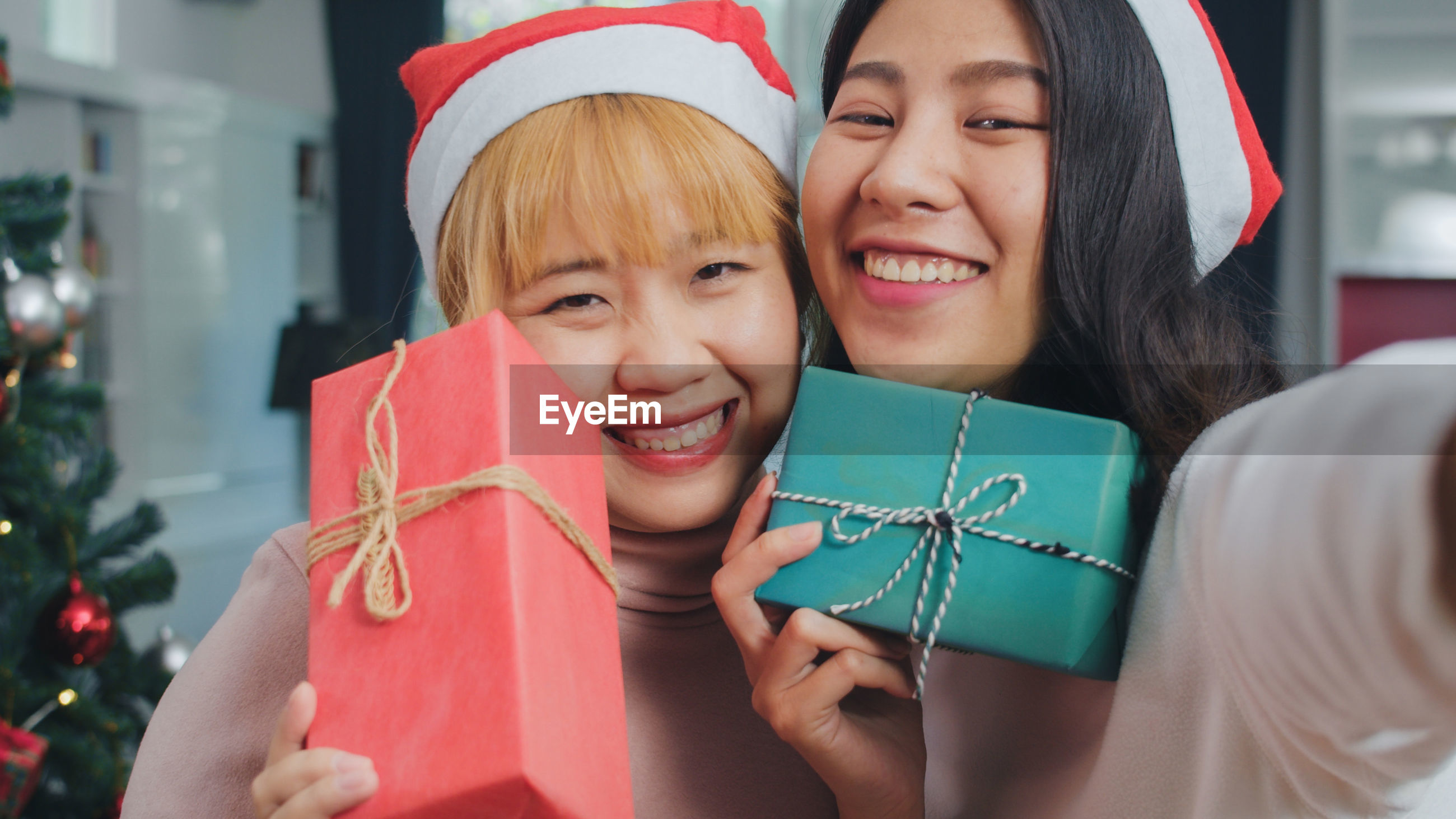 Portrait of smiling women holding gifts while standing at home